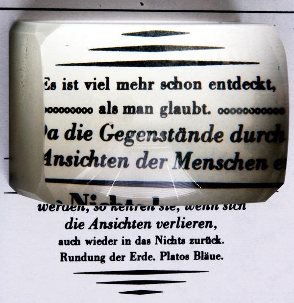 Blick durch einen modernen Lesestein auf einen Text Quelle: Hedwig Storch (CC BY-SA 3.0)